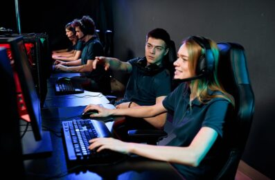 Young cyber sport gamer giving advice to girl in headphones while they preparing for e-sport competition